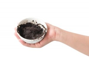 Woman's hand holding bowl of coffee grounds for skin scrub health care and beauty concept